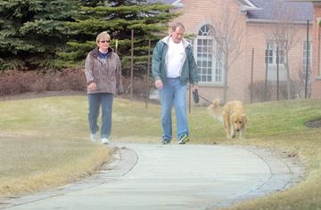 Peter and Jane Keast are out for a walk in their neighbourhood at the Ballantrae Golf and Country Club with their dog Buddy.