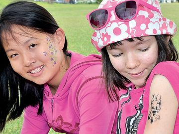 Sharon Lou,10, left and Alina Khaibullina, 11, get temporary tattoos.