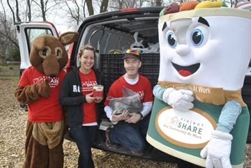 Katie Cuviello and Stephen Priddle , with Project Share mascots Phyllis and Phillip, collect food donations at the Stamford Centre Volunteer Firefighters Association's Easter Egg Hunt at Firemen's Park on Friday