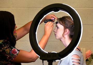 Jordanna Hale applies makeup to Grade 10 student Mary Pickford.