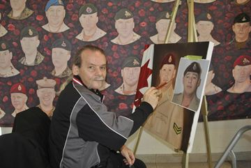 David Sopa works on a portrait of a fallen hero with his expansive work in the background on display at the Niagara Home and Garden Show in Grimsby at the Peach King Centre on Saturday.