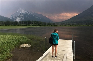 A woman takes in the smoke blanketing Mt. Rundle from a forest fire in Kootenay National park as she stands on a dock on the Vermillion lakes near Banff, Alta. Sunday July 15, 2017. THE CANADIAN PRESS/Adrian Wyld