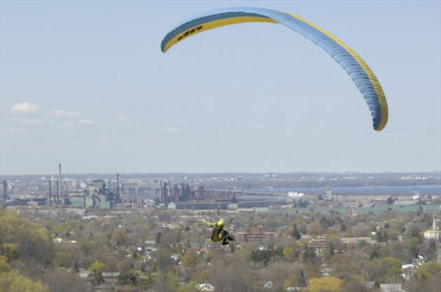 A parasailer soars over King's Forest Golf Club. The city has installed extra fencing and signs to discourage the sport.