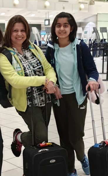 A woman and a girl stand in an airport with luggage