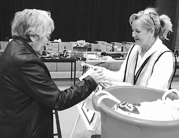McNab Public School principal Tracey Stevenson sells a two-dollar bargain bag to Beatrice Gilmour of White Lake to fill with as much as she wants at the school's multi-family mega garage and bake sale Saturday morning to raise money for kitchen renovations at the school. All proceeds support the students programs and resources.