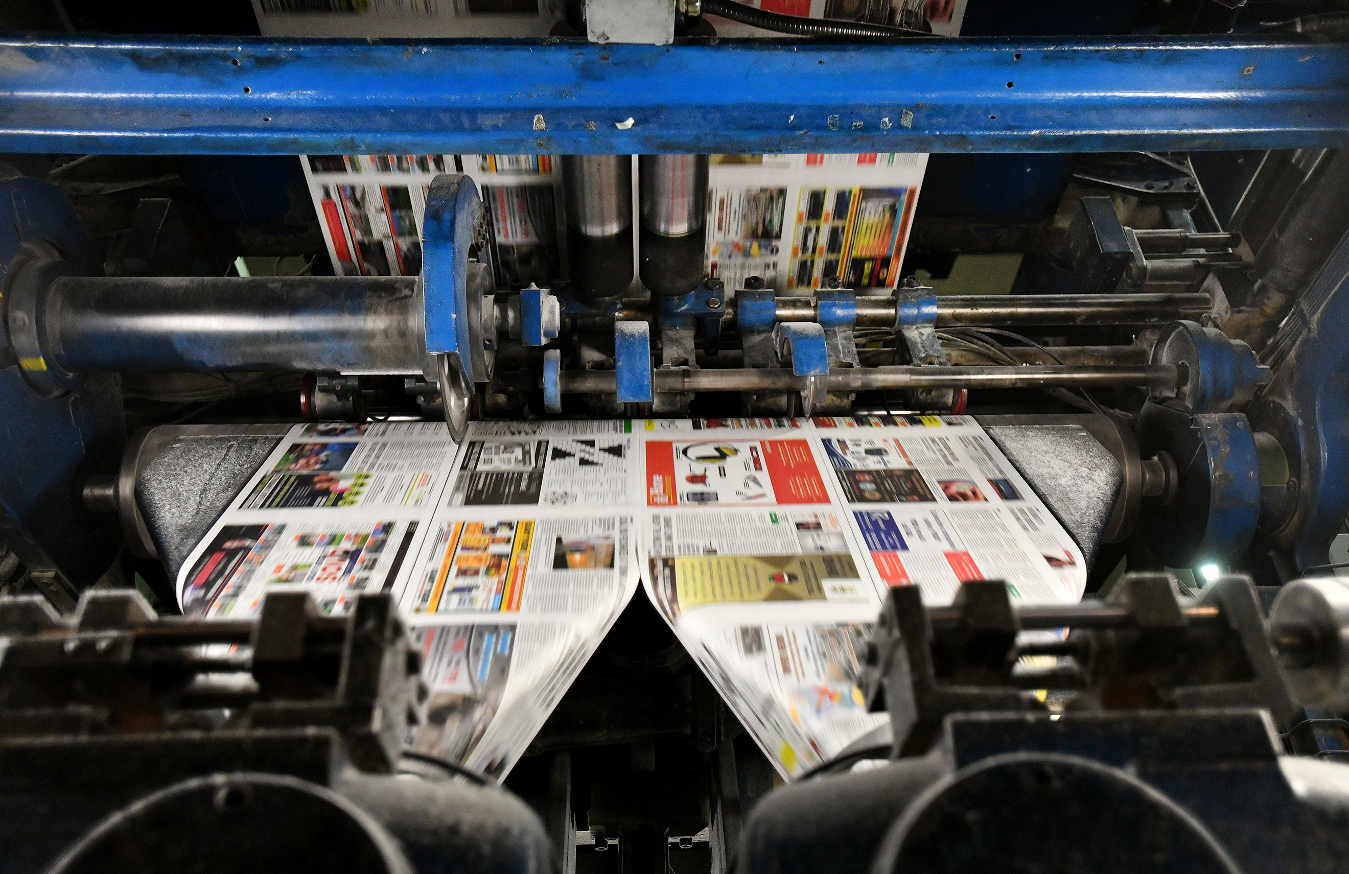 Papers being printed on the blue press.