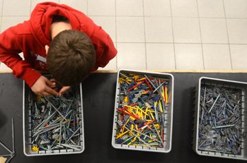 A student sorts through the bins, looking for the right pieces.