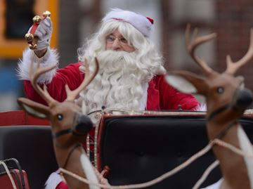 The man of the hour waves to the crowd as the annual Stoney Creek Santa Claus Parade made its way down King Street East in old Stoney Creek Saturday much to the delight of the thousands of spectators who lined the street.