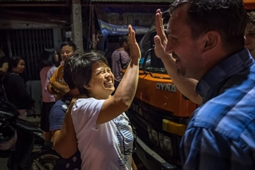 Onlookers in front of Chiangrai Prachanukroh Hospital watch and cheer as ambulances transport the last rescued schoolboys and their coach from a helipad nearby to Chiangrai Prachanukroh Hospital on July 10, 2018 in Chiang Rai, Thailand. The successful effort to rescue the soccer team ended Tuesday.