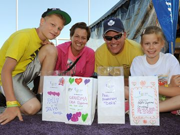 The Elgersma family — mom Diane, dad Mark and their two kids Taylor (left) and Taryn (right) — prepare luminaries to be placed trackside before taking part in the 12-hour Relay for Life on Friday (June 14).