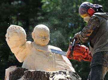 Aya Blaine meticulously removes material to reveal her carving of a child cancer survivor.