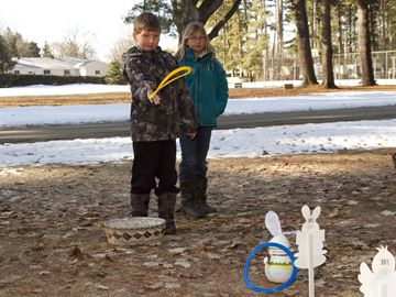 Seven-year-old Corey Cox plays some ring toss as his 9-year-old sister Kristina watches.