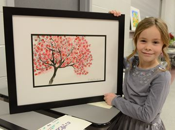 Isabelle Woods, 8, holds up her work during an art exhibition by Soo Yun's students at Tansley Woods on Saturday afternoon. For more information on Art for Life go to http://sooyunartforlife.blogspot.ca.