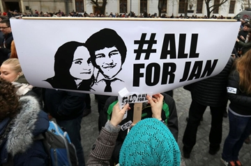A woman sticks a sticker on a poster with a photo of slain journalist Jan Kuciak during an anti-government rally in Bratislava, Slovakia March 9. The country-wide protests demanded a thorough investigation into the shooting deaths of Jan Kuciak and Martina Kusnirova, whose bodies were found in their home on Feb. 25, and changes in the government.