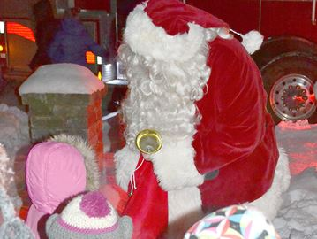 Santa Claus greets children at Station Park in Stayner Friday night during the Stayner Chamber of Commerce's Christmas carol sing and tree light up event.