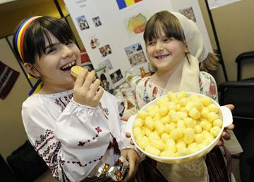 At the Romania booth, Stefania Dragalin ,left, enjoys a Eugenia biscuit as her friend Ana Nastase  holds a bowl of Transilvania puffs , a well known treat.