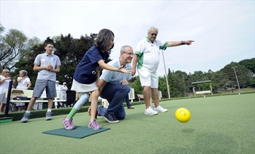 Neva Podgiaz-Harrigan takes a shot with MP Borys Wrzesnewskyj while member Rick Nytko guides them during the James Gardens Lawn bowling Club's annual War Amps event Saturday, July 4.