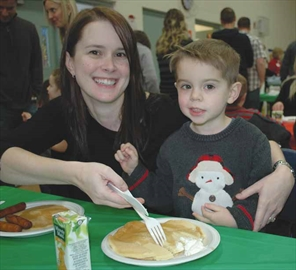 Lisa and Torren Smyth enjoy some pancakes, sausage and orange juice at the Riverside South Community Association's pancake breakfast on Nov. 30.