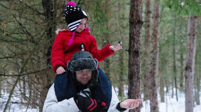 Claire Tellier, five, sits on the shoulders of her father, Dave, to feed the chickadees at the Christmas Party For The Animals.