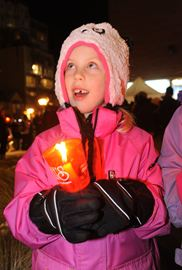 Here, Ava Schuit ,6, looks up to the holiday lights as she sings Christmas carols out front the Performing Arts Centre.