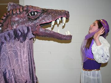 Genie Anika Putnam is threatened by the dragon backstage at dress rehearsal for NFLT's production of Aladdin and his Wonderful, Magical Lamp. The dragon was made by Mike and Jocelyn Steeves after a plan to use the crocodile from Peter Pan was scrapped.