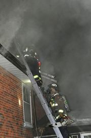 Here, firefighters encounter thick smoke as they work to ventilate the fire.