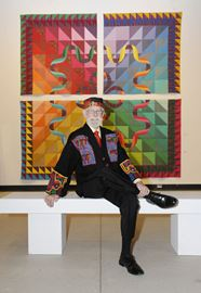 Here, John Willard strikes a pose infront of this giant four panel , entitled ' 100+20 ÷ 4 =3 , is part of the Town of Oakville quilt collection.