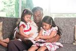 Grandfather reading with his granddaughters