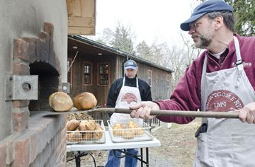 Volunteers Anton DeGiusti, left, and Dale Howey pull fresh loaves of bread from the oven, after arriving early to prepare dozens of loaves for sale to the public, Wednesdays from 3 to 5 p.m. Money raised helps support programs at Montgomery's Inn. (March 27, 2013)