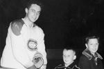 Jean Beliveau (left) hands a signed stick to a young Mike Drynan.