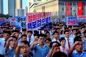 ADDS TRANSLATION OF SIGN - Tens of thousands of North Koreans gather for a rally at Kim Il Sung Square carrying placards and propaganda slogans as a show of support for their rejection of the United Nations' latest round of sanctions on Wednesday Aug. 9, 2017, in Pyongyang, North Korea. Propaganda poster at center says,