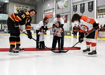 Elle Morton, centre, and her family get ready to drop the ceremonial puck to Paris Mounties captain Ian Fowler, left, and Burford Bulldogs assistant captain Tommy Smith on Saturday night at the Brant Sports Complex.
