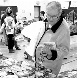 Christine Leskie of Renfrew checks out the books available for purchase at the McNab Public school mega garage and bake sale.