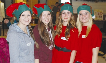 Santa's elves at the Fitzroy Harbour Community Centre last Saturday include Molly Burke and Christine Noel, left photo, and Erin Chartrand, Adrienne Jones, Tiffani McMurray, and Rylie McManus. Meanwhile, enjoying cake for lunch during the children's Christmas party are Ivy and Logan Trudeau of Kinburn.