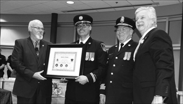 Bill McKim, executive director of the Ontario Municipal Management Institute, presented Robert Comeau, Quinte West's fire prevention officer, with a certificate recognizing his achievement of becoming a Certified Municipal Manager in fire prevention enhancement. Fire Chief John Whelan and Mayor John Williams are pictured on the right.