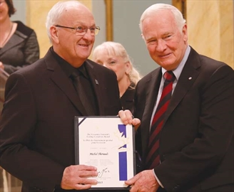 Michel Thériault from Orléans receives the Caring Canadian Award from Gov.-Gen. David Johnston on April 17 along with Suzanne Thériault for their work volunteering with the Roy G. Hobbs Seniors' Club, tripling the club's membership during their time as president and vice-president.