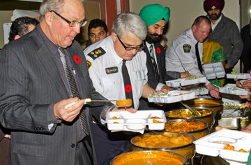Councillor Ron Simpson and South Simcoe Police Service Chief Rick Beazley sample some of the food.
