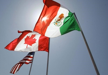 In this April 21, 2008 file photo, national flags of the United States, Canada, and Mexico fly in the breeze in New Orleans. The Canadian government is getting kudos from unions for proposing that both Mexico and the United States commit to improved labour standards in a rewritten North American free trade agreement. THE CANADIAN PRESS/AP/Judi Bottoni