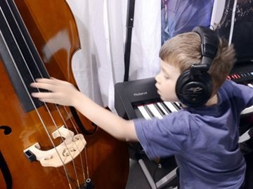 Ciaran Ferguson, 4, is a multi-instrumentalist musician as he plays the piano and strums the double base in the Connors Music booth at the Georgina Home & Lifestyle Show at the Georgina Ice Palace May 11.