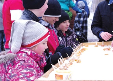 Children wait patiently as volunteers prepare maple syrup taffy outside of the Vanier Maple Sugar Shack on April 5. Just one part of the Maple Sugar Festival's activities, grown-ups and children alike had a taste of the sweet stuff.