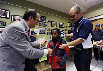 Jaime Libaque (left) and Rex Catubig help David Isaac-Olobor, 6, with his new jacket at the Local Knights of Columbus winter coat distribution to children from refugee and other newcomer families at the Dorset Park Hub, which is run by Agincourt Community Services Association.