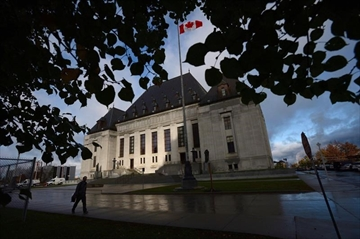 A pedestrian walks past the Supreme Court of Canada in Ottawa, Oct. 18, 2013. The Supreme Court will decide this morning whether the federal government can rely on National Energy Board reviews to fulfills its duty to consult indigenous communities before development can take place on their traditional territories. THE CANADIAN PRESS/Sean Kilpatrick