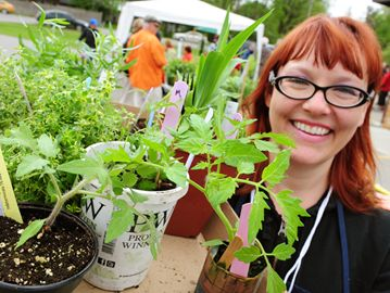 Kelly Olson is ready to head back to plant this selection of herbs, heirloom tomatoes and day lillies in her garden.