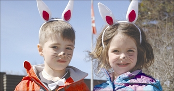 Recently moved into the area, Andrew (7) and Claire Mosher (5), interrupt their first Bunny Hop experience to show offtheir bunny ears during the Easter Bunny Hop.