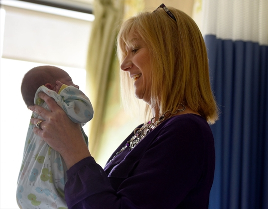 Sarah Simpson, a social worker, comforts a baby in the St. Joseph Neonatal Intensive Care Unit.