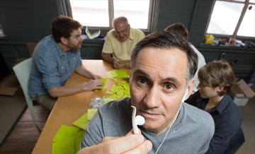 "Kirk Mosna, foreground, holds up ""Spring"" a clip created by Hamilton design firm OHM, that attaches to the latest Apple earbuds preventing them from dropping out of the ear while running or working out."