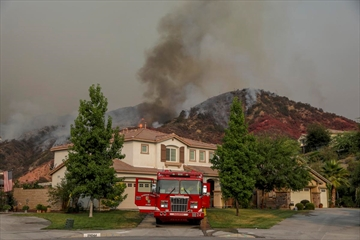 A structure protection fire engine is stationed at a house on 29000 block of Point Shore Dr. in McVicker Canyon neighborhood as Holy Fire burns on hills behind on Aug. 8, 2018 in Lake Elsinore, Calif. The Holy fire in Cleveland National Forest grew significantly over the last day, burning a total of 9,614 acres by Thursday morning and pushing closer to some Riverside County homes.