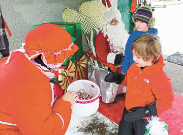 Simon and Parker Pirso get treats form Mrs. Claus at Phin Avenue Park in The Pocket neighbourhood.