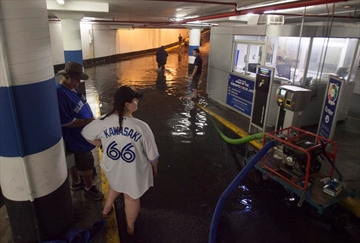 Toronto Blue Jays fans get stuck in the Rogers Centre as the entrance to the parking garage floods with torrential rain, in Toronto on Tuesday.