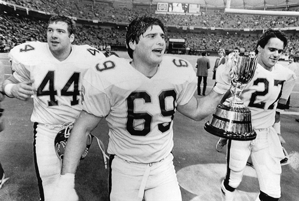Toronto Argonaut offensive lineman Dan Ferrone carries the Grey Cup as the Argos celebrate winning the 1983 CFL championship.